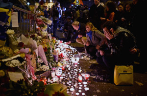 PARIS, FRANCE - NOVEMBER 14: People place flowers and candles on the pavement near the scene of yesterday's Bataclan Theatre terrorist attack on November 14, 2015 in Paris, France. At least 120 people have been killed and over 200 injured, 80 of which seriously, following a series of terrorist attacks in the French capital. (Photo by Jeff J Mitchell/Getty Images)